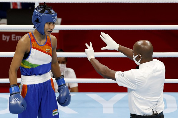 epa09393361 Referee Wilfredo Vazquez Calero (R) gestures in front of Lovlina Borgohain of India (blue) during her bout in the Women's Fly (48-51kg) Semifinal against Busenaz Surmeneli of Turkey (red) during the Boxing events of the Tokyo 2020 Olympic Games at the Ryogoku Kokugikan Arena in Tokyo, Japan, 04 August 2021.  EPA/RUNGROJ YONGRIT