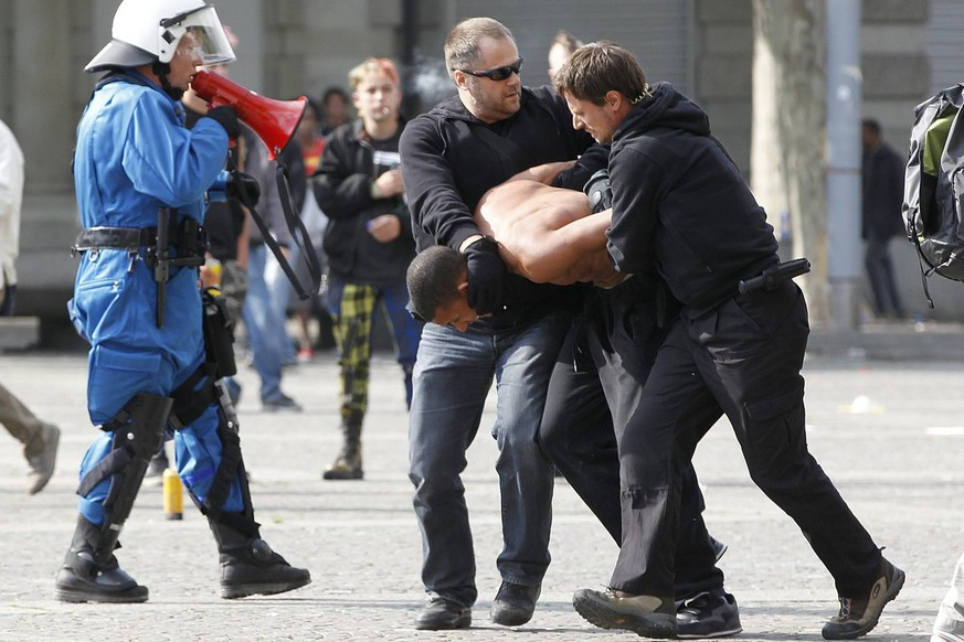 Plainclothes police officers arrest a young man on the Helvetiaplatz square after a labour day demonstration in Zurich, Switzerland, Sunday, on May 1, 2011. (KEYSTONE/Alessandro Della Bella)