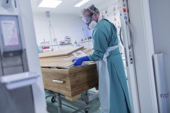 FILE - In this Dec. 18, 2020 file photo, funeral director Christoph Kuckelkorn closes a coffin containing a deceased person who died of or with the coronavirus in Cologne, Germany. Germany announced 26,391 new cases and 1,070 deaths today. (Rolf Vennenbernd/dpa via AP, File)