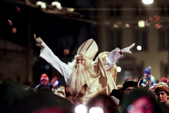 St. Nikolaus reitet auf dem Esel durch die Strassen am Samstag, den 2. Dezember 2017 in Freiburg. Alljaehrlich am 1. Dezemberwochenende versammeln sich tausende Leute, wenn der St. Nikolaus auf dem Ruecken eines Esels durch die Strassen reitet und Lebkuchen an die Kinder verteilt. (KEYSTONE/Christian Merz)