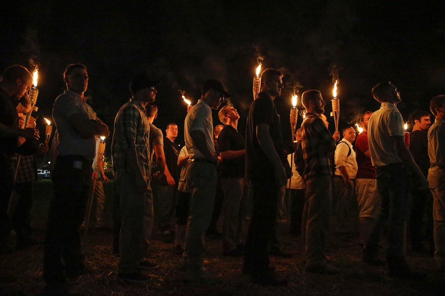 In this Friday, Aug. 11, 2017, photo, multiple white nationalist groups march with torches through the University of Virginia campus in Charlottesville, Va. Forty-six-year-old Tyler Magill, a librarian at UVA suffered a stroke Tuesday, Aug. 15. Doctors say the stroke resulted from an injury an artery in his neck. Friends say he suffered that injury when a white supremacist lobbed a lit torch at Magill's neck Friday night at the rally. (Mykal McEldowney/The Indianapolis Star via AP, File)