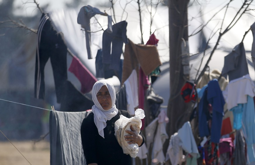 A migrant woman walks through the makeshift refugee camp at the northern Greek border point of Idomeni, Greece, Wednesday, March 30, 2016. Hundreds of migrants and refugees have arrived on Greek islands after days of low numbers, despite a European Union-Turkey agreement under which new arrivals will be sent back to Turkey. Figures released by the Greek government Wednesday showed 766 people reached the islands of Lesbos, Samos, Chios and Kos in the 24 hours until Wednesday morning. (AP Photo/Darko Vojinovic)