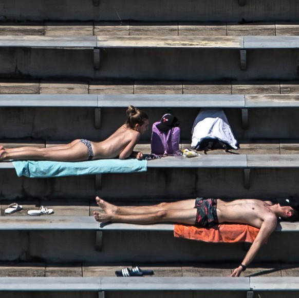 epaselect epa06920120 People sunbathe during warm weather on the spectators' ranks at a swimming pool area in Prague, Czech Republic, 31 July 2018. A current heat wave brings temperatures of about 35 degrees Celsius across Czech Republic and many other parts of Europe.  EPA/MARTIN DIVISEK