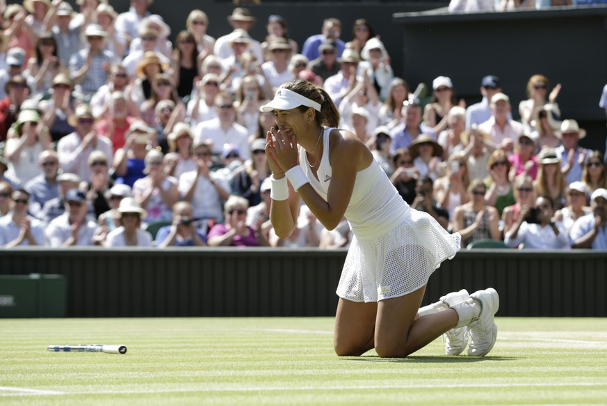 Garbine Muguruza of Spain falls on her knees after defeating Agnieszka Radwanska of Poland during their women's singles semifinal match at the All England Lawn Tennis Championships in Wimbledon, London, Thursday July 9, 2015. Muguruza won 6-3, 3-6, 6-3. (AP Photo/Alastair Grant)