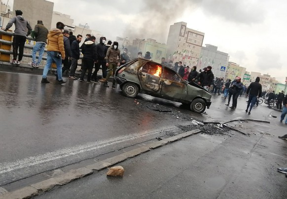 epa08002045 Iranian protesters stand around a vehicle set ablaze during clashes following fuel price increase in Tehran, Iran, 16 November 2019. Media reported that people protested on highways a day after the government increased fuel price by at least 50 percent.  EPA/STRINGER