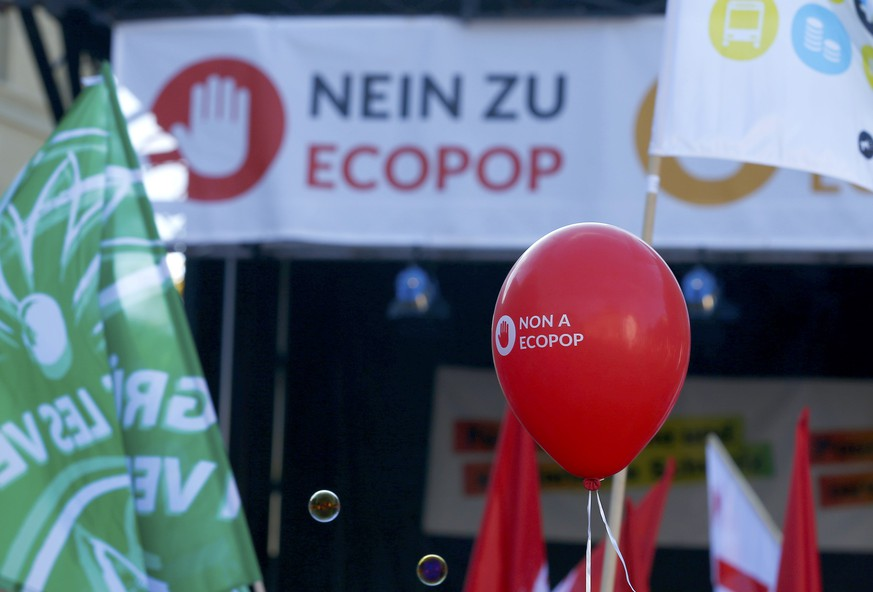 Banners and a balloon against the Ecopop initiative are carried by protestors during a demonstration in Bern November 1, 2014. Swiss voters will decide in a referendum on November 30 whether they want to cap immigration at just 0.2 percent of the resident population or the equivalent of 16,000 people per year.  REUTERS/Ruben Sprich (SWITZERLAND  - Tags: SOCIETY IMMIGRATION POLITICS)