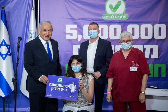 epa09061476 Israeli Prime Minister Benjamin Netanyahu (L) and his Health Minister Yuli Edelstein (C) mee with the Israeli citizen (C) no. 5,000,000 that get the Pfizer-BioNTech COVID-19 vaccine against the Covid-19 in Tel Aviv, Israel, 08 March 2021.  EPA/MIRIAM ALSTER / POOL