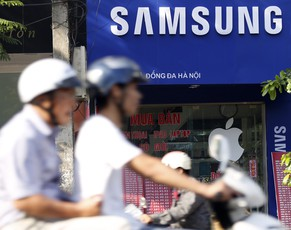 epa04305025 Two men ride past a Samsung mobile shop on a street in Hanoi, Vietnam, 08 July 2014. According to local media reports Samsung plans to build a one billion US dollar display manufacturing plant in Bac Ninh province, Vietnam in 2015.  EPA/LUONG THAI LINH