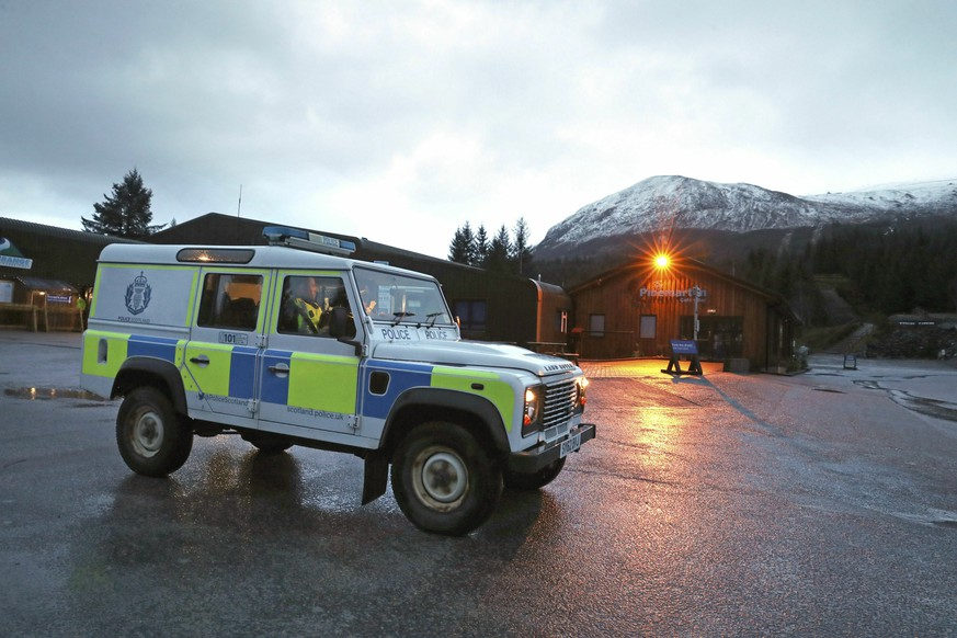 A police vehicle at the Nevis Range Mountain Resort with Ben Nevis in the background, in Scotland, Tuesday March 12, 2019. Police in Scotland say an avalanche has killed two people on Britain's highest mountain. It was reported that a group of climbers were on Ben Nevis mountain when the avalanche came down shortly before noon on Tuesday. (Andrew Milligan/PA via AP)
