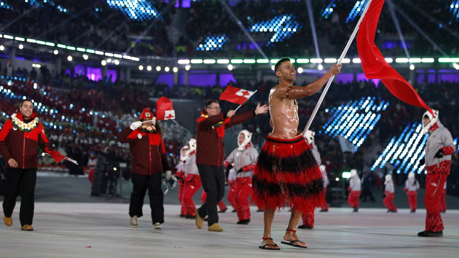 Pita Taufatofua carries the flag of Tonga during the opening ceremony of the 2018 Winter Olympics in Pyeongchang, South Korea, Friday, Feb. 9, 2018. (AP Photo/Jae C. Hong)