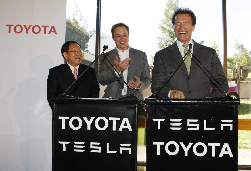 From left, Toyota CEO Akio Toyoda, Tesla CEO Elon Musk, and Calif. Gov., Arnold Schwarzenegger laugh during a news conference at Tesla headquarters in Palo Alto, Calif., Thursday, May 20, 2010. Tesla will partner with Toyota Motors Corp. to build electric cars at a recently shuttered auto plant in the San Francisco Bay area. (AP Photo/Paul Sakuma)