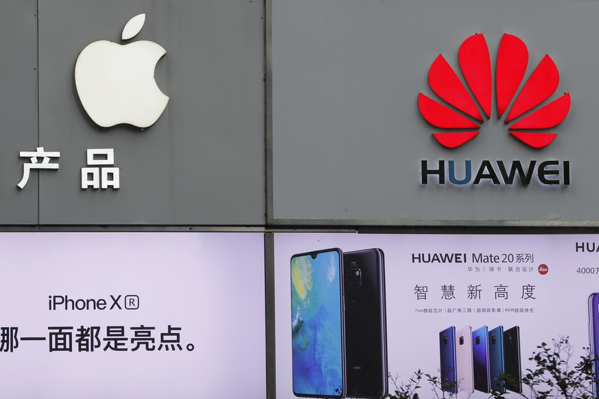 Logos of Apple and Huawei are displayed outside mobile phone retail shop in Shenzhen, China's Guangdong province, Thursday, March 7, 2019. Chinese tech giant Huawei is challenging a U.S. law that labels the company a security risk and would limit its access to the American market for telecom equipment. (AP Photo/Kin Cheung)