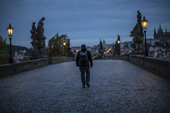 epa08737225 A man walks on the Charles Bridge early morning in Prague, Czech Republic, 12 October 2020. Czech government decided from 12 October all cultural, sporting and social events, services, dance association events, both amateur and professional, are canceled due to new measures in connection with the COVID-19 pandemic caused by the SARS-CoV-2 coronavirus. Czech Republic had record rise in COVID-19 disease, increase in newly detected infections exceeded 8,000 last week.  EPA/MARTIN DIVISEK