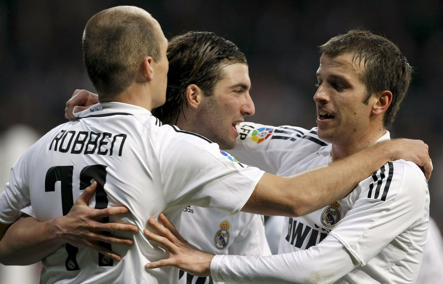 epa01603769 Real Madrid's Argentinian forward Gonzalo Higuain (C) celebrates with his teammates Dutch striker Arjen Robben (L) and Dutch midfielder Rafael van der Vaart (R) after scoring second goal against Osasuna during their Spanish Primera Division soccer match at Santiago Bernabeu stadium in downtown Madrid, central Spain, 18 January 2009.  EPA/Ballesteros
