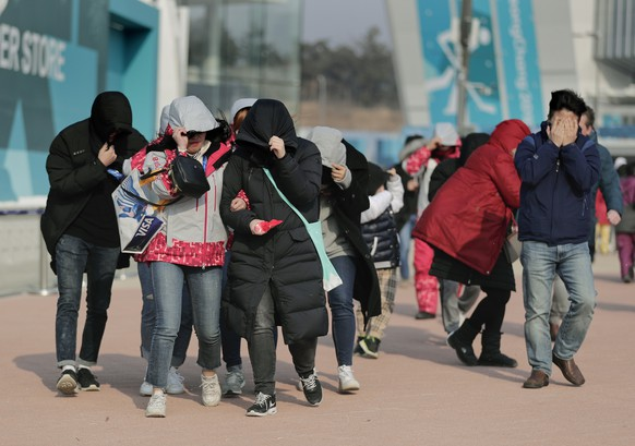 Visitors to Gangneung Olympic Park shield themselves from blowing dirt and debris from strong winds as they leave the park at the 2018 Winter Olympics in Gangneung, South Korea, Wednesday, Feb. 14, 2018. Spectators were advised to either stay inside competition venues or leave the park because of high winds. (AP Photo/Julie Jacobson)
