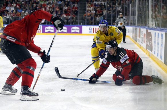Sweden's Elias Lindholm, center, challenges for the puck with Canada's Mitch Marner during the Ice Hockey World Championships final match between Canada and Sweden in the LANXESS arena in Cologne, Germany, Sunday, May 21, 2017. (AP Photo/Petr David Josek)