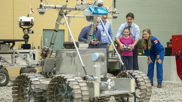 Canada's Prime Minister Justin Trudeau and his daughter, Ella-Grace, and astronaut Jenni Sidey-Gibbons drive a Juno six rover during a visit to the Canadian Space Agency headquarters , Thursday, Feb, 28, 2019 in St. Hubert, Quebec. Trudeau announced Thursday that Canada will take part in an international lunar space station project. (Ryan Remiorz/The Canadian Press via AP)