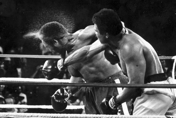 FILE - This is a Oct. 30, 1974  file photo perspiration flies from the head of George Foreman as he takes a right from challenger Muhammad Ali in the seventh round in the match dubbed Rumble in the Jungle in Kinshasa, Zaire.  Foreman was knocked out in the eighth round. It was 40 years ago that two men met just before dawn on Oct. 30, 1974, to earn $5 million in the Rumble in the Jungle. In one of boxing's most memorable moments, Muhammad Ali stopped the fearsome George Foreman to recapture the heavyweight title in the impoverished African nation of Zaire.  (AP Photo/Ed Kolenovsky, File)