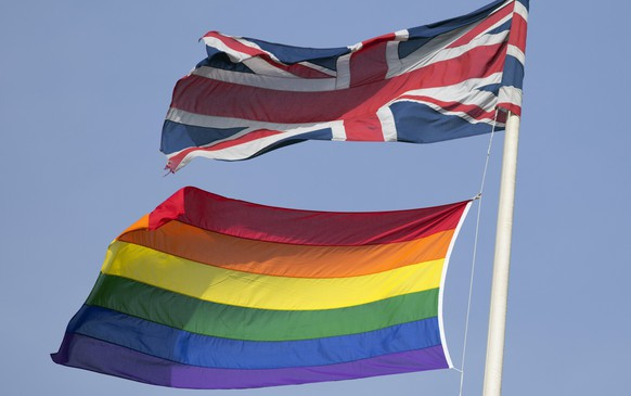 A rainbow flag flies with the Union flag above British Cabinet Offices, marking the first day Britain has allowed same sex marriages, in London March 29, 2014. Prime Minister David Cameron hailed Britain's first gay marriages on Saturday, saying marriage was not something that should be denied to anyone because of their sexuality. Campaigners have spent years battling to end a distinction that many gay couples say made them feel like second class citizens and Saturday was the first day that gay couples could tie the knot in England and Wales. REUTERS/Neil Hall (BRITAIN - Tags: POLITICS SOCIETY)
