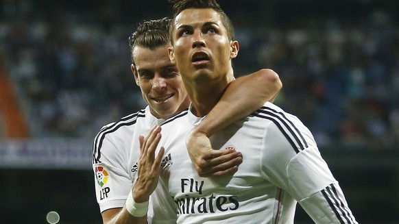Real's Cristiano Ronaldo, second left, celebrates his goal with Real's Gareth Bale, left, during a Spanish La Liga soccer match between Real Madrid and Elche at the Santiago Bernabeu stadium in Madrid, Spain, Tuesday, Sept. 23, 2014. (AP Photo/Andres Kudacki)