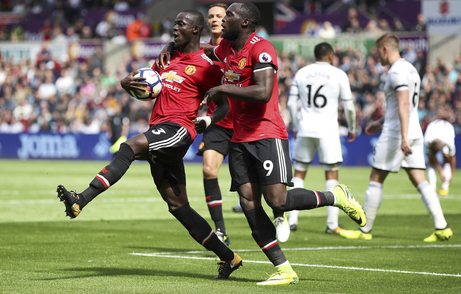 Manchester United's Eric Bailly, left, celebrates with teammate Romelu Lukaku after scoring his side's first goal during their English Premier League soccer match at the Liberty Stadium, Swansea, Wales, Saturday, Aug. 19, 2017. (Nick Potts/PA via AP)
