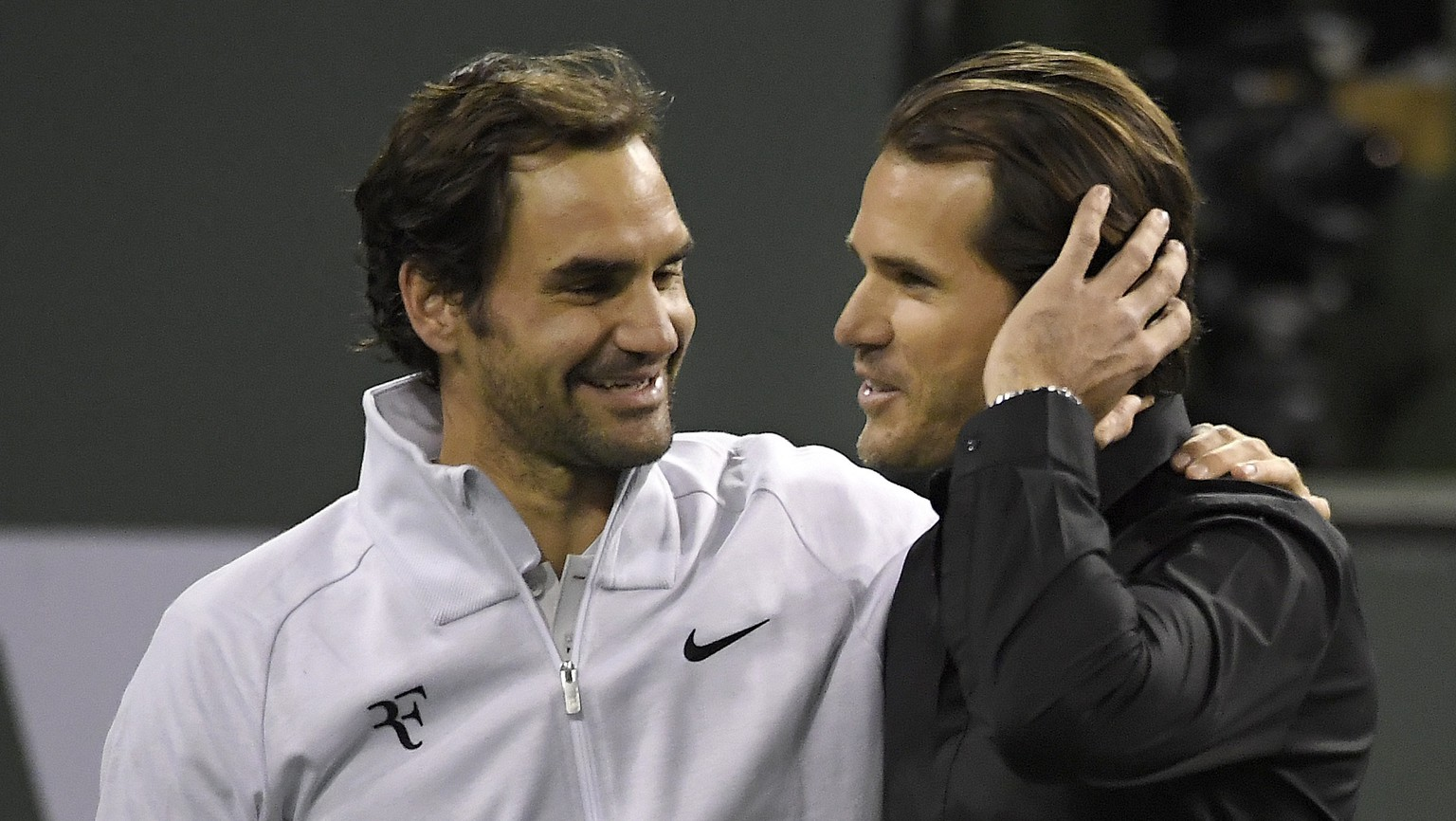 Roger Federer, left, of Switzerland, greets Tommy Haas, of Germany, after Haas announced his retirement following Federer's quarterfinal match against Chung Hyeon at the BNP Paribas Open tennis tournament Thursday, March 15, 2018, in Indian Wells, Calif. (AP Photo/Mark J. Terrill)