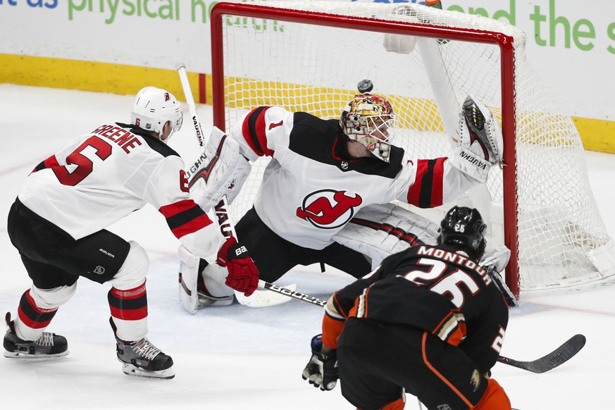 Anaheim Ducks' Brandon Montour, foreground, scores against New Jersey Devils goaltender Keith Kinkaid during the third period of an NHL hockey game Sunday, March 18, 2018, in Anaheim, Calif. The Ducks won 4-2. (AP Photo/Jae C. Hong)
