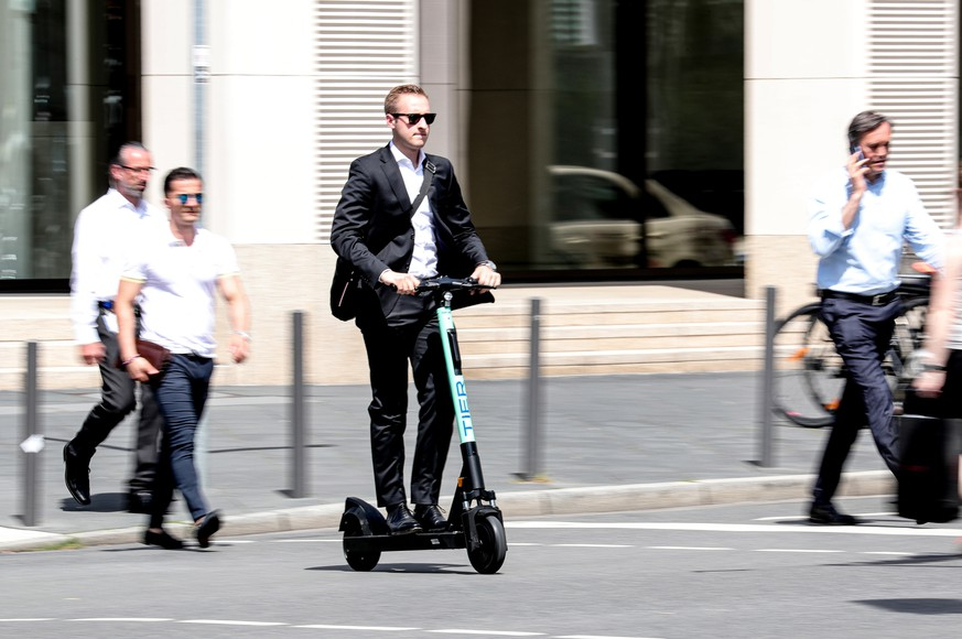 epa07672467 A man uses an e-scooter in downtown Frankfurt Main, Germany, 25 June 2019. 'Tier Mobility' company starts the business of renting e-scooters since last weekend. The company is already providing e-scooters renting service in around 20 European cities and several in Germany including Berlin, Cologne and Hamburg.  EPA/ARMANDO BABANI
