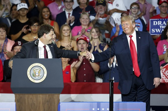 President Donald Trump, right, shakes hands with 12th Congressional District Republican candidate Troy Balderson, left, during a rally, Saturday, Aug. 4, 2018, in Lewis Center, Ohio. (AP Photo/John Minchillo)