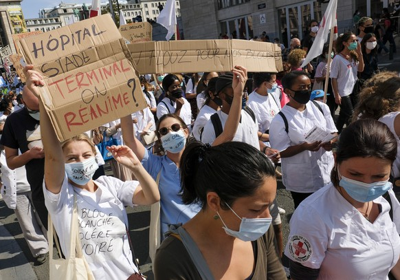 epa08666374 People wearing face masks carry placards during a Health Sector protest in Brussels, Belgium, 13 September 2020. Workers, patients, caregivers and associations of the health sector unite to demand the refinancing of health care and oppose the growing macro-commodification of the sector.  EPA/JULIEN WARNAND