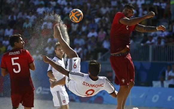 Dejan Stankovic (C) of Switzerland kicks the ball next to Jordan Santos (L) and Rui Coimbra of Portugal during their group stage beach soccer match at the 1st European Games in Baku, Azerbaijan, June 24, 2015. REUTERS/Kai Pfaffenbach