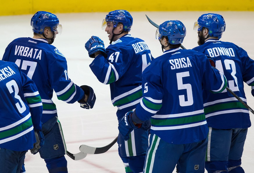 Vancouver Canucks' Sven Baertschi (47), of Switzerland, celebrates his goal with teammates Radim Vrbata (17), of the Czech Republic; Luca Sbisa (5), of Switzerland; and Nick Bonino (13) during the second period of an NHL hockey game against the Edmonton Oilers in Vancouver, British Columbia, Saturday, April 11, 2015. (AP Photo/The Canadian Press, Darryl Dyck)