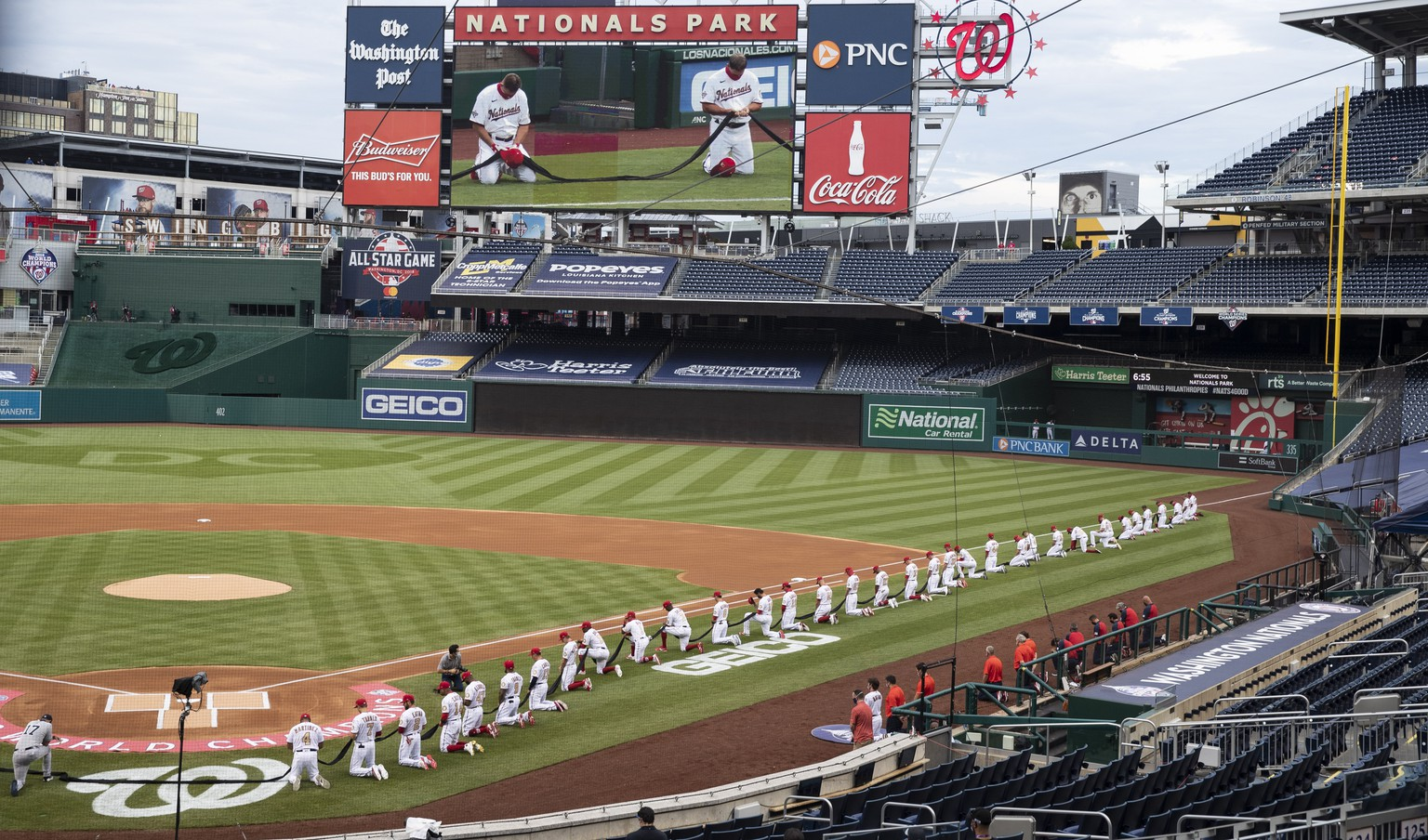Members of Washington Nationals and against the New York Yankees kneel and hold a piece of black fabric before an opening day baseball game at Nationals Park, Thursday, July 23, 2020, in Washington. (AP Photo/Alex Brandon)