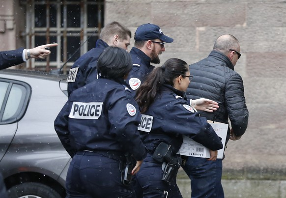 Former Kosovo prime minister Ramush Haradinaj, right, is rushed by police officers inside the Colmar courthouse, eastern France, Thursday Jan.5, 2017. Haradinaj is facing possible extradition to Serbia to face war crimes charges after being arrested at a French airport. (AP Photo/Jean-Francois Badias)