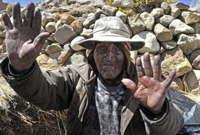 (FILE) Picture taken on August 15, 2013 of Bolivian Carmelo Flores Laura, an Aymara native who claims is 123 years old and if confirmed would be the oldest man alive, waves outside his house in the community of Frasquia, 4050 metres above sea level, on the foothills of the Illampu snowcapped mountain in the Bolivian Andes, some 150 km east of La Paz. Flores Laura died on the eve, a doctor and a family member announced on June 10, 2014.   AFP PHOTO / Aizar RALDES