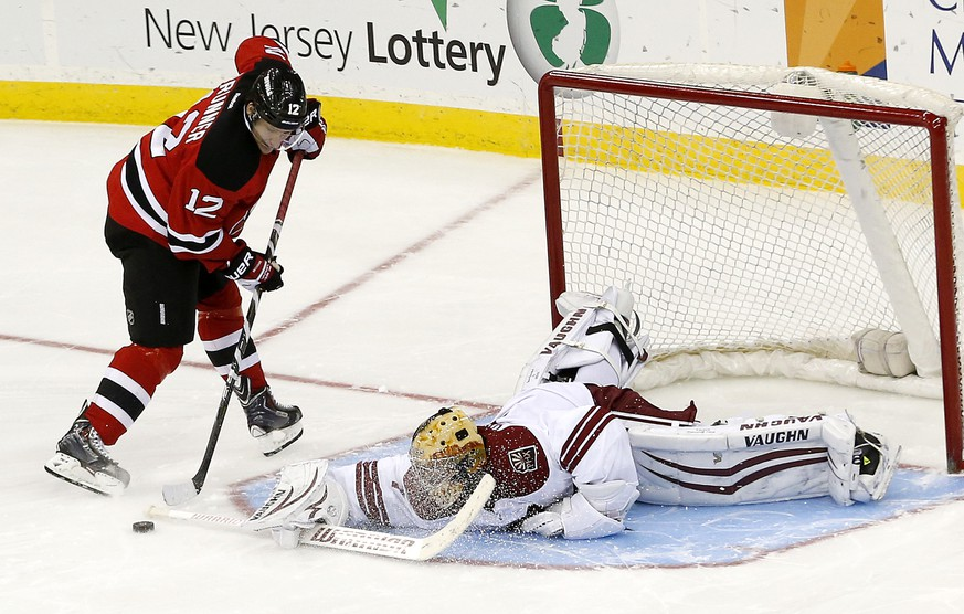 Phoenix Coyotes goalie Thomas Greiss, right, of Germany, lays out to block a shot by New Jersey Devils ring wing Damien Brunner, of the Czech Republic, during a shootout in an NHL hockey game, Thursday, March 27, 2014, in Newark, N.J. The Coyotes won 3-2. (AP Photo/Julio Cortez)