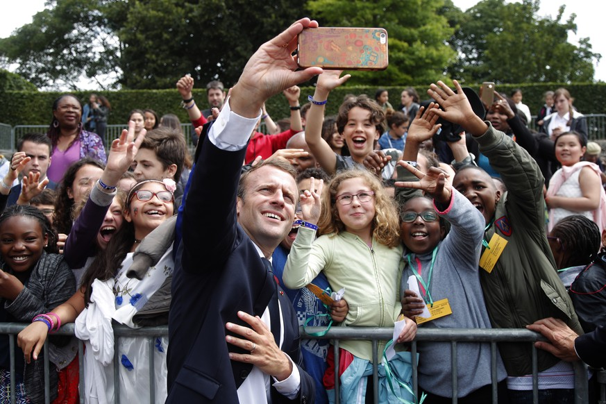 epa06818866 French President Emmanuel Macron takes selfies with children during a ceremony marking the 78th anniversary of late French General Charles de Gaulle's resistance call of June 18, 1940, at the Mont Valerien memorial in Suresnes, near Paris, France, 18 June 2018.  EPA/CHARLES PLATIAU / POOL MAXPPP OUT