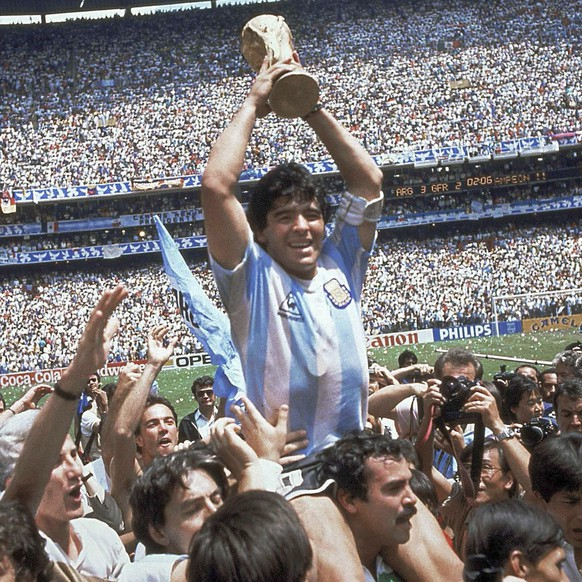 FILE - In this June 29, 1986 file photo, Diego Maradona holds up the trophy after Argentina defeated West Germany 3-2 during a World Cup soccer final match at Atzeca Stadium in Mexico City. The Argentine soccer legend says he favors the use of video referees, but appreciates the technology didn't exist in 1986 when he made his famous goal against England using his hand that became known as