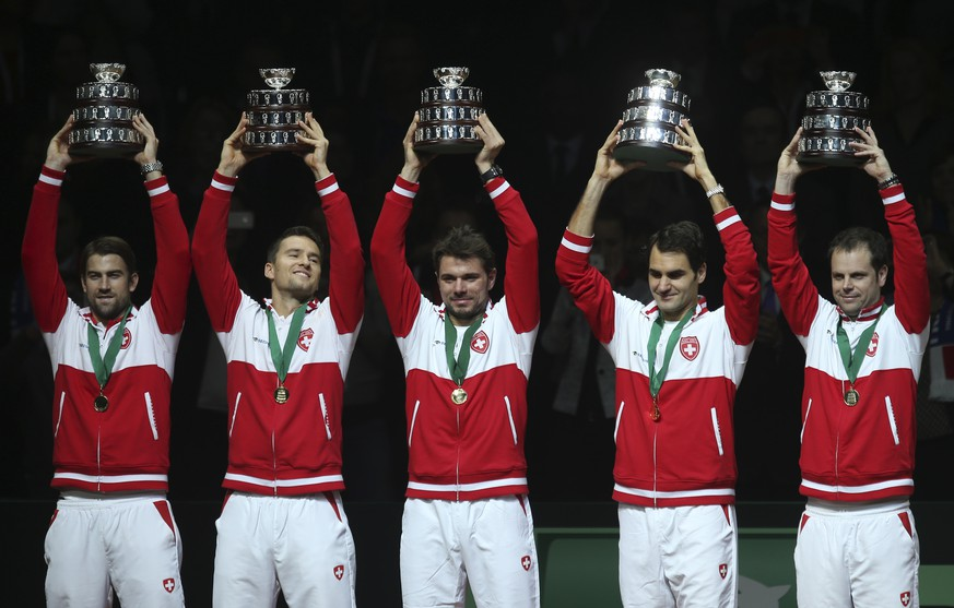 Swiss team, from the left, Michael Lammer, Marco Chiudinelli, Stanislas Wawrinka, Roger Federer and coach Severin Luthi hold their trophy after winning the Davis Cup final at the Pierre Mauroy stadium in Lille, northern France, Sunday, Nov. 23, 2014. Federer won 6-4, 6-2, 6-2 to give Switzerland a 3-1 lead and victory. (AP Photo/Peter Dejong)