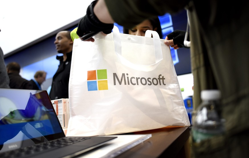 epa04997610 A customers holds a bag in the new Microsoft flagship store on Fifth Avenue in New York, New York, USA, on 26 October 2015. The large store opens today and coincides with the release of the company's new products that go on sale today, including the Surface Book and Surface Pro 4.  EPA/JUSTIN LANE