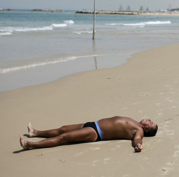 A man lies on the sand at the beach in Tel Aviv, Israel, May 27, 2015. A heatwave settled over Israel on Wednesday, with temperatures reaching near 45 Celsius (113 Fahrenheit), according to Israel's Metereological Service. REUTERS/Baz Ratner