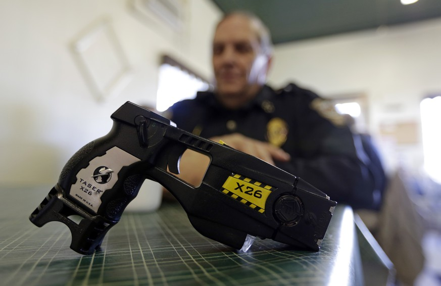 FILE - In this Nov. 14, 2013, file photo, a Taser X26 sits on a table in Knightstown, Ind. In the recent shootings of unarmed black men in a San Diego suburb and in Tulsa, Oklahoma, the police officers who fired the fatal shots were accompanied by officers who simultaneously drew their stun guns. Civil rights advocates say the different response by officers facing the same suspect and the same apparent threat illustrates a breakdown in police training and communication and shows that some officers are too quick to turn to deadly force.  (AP Photo/Michael Conroy, File)