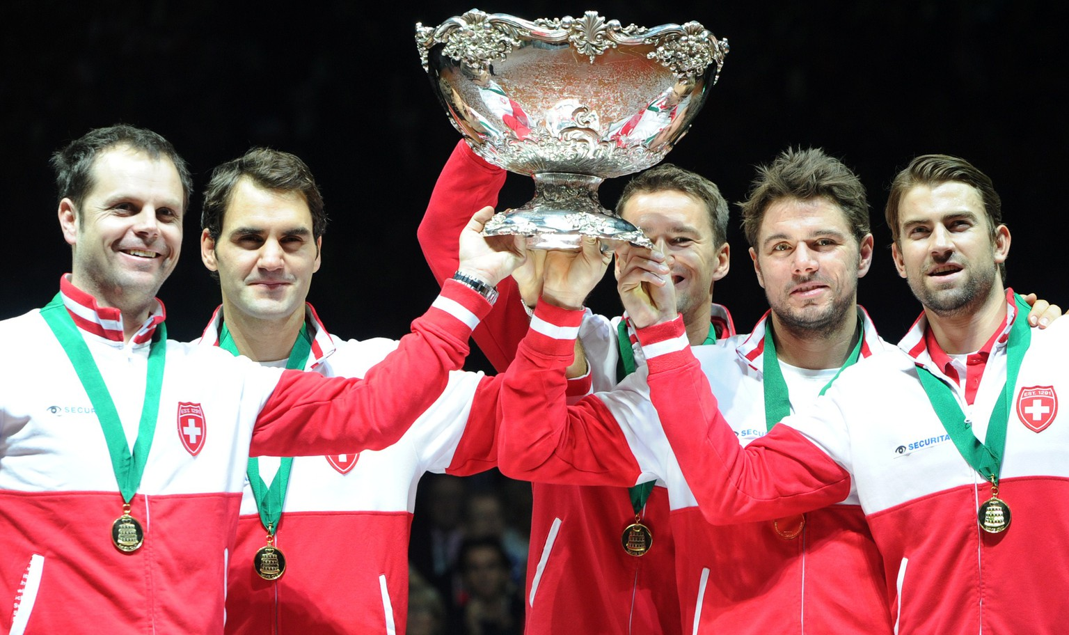 (L-R) Switzerland's Davis Cup team captain Severin Luthi and tennis players Roger Federer, Stanislas Wawrinka, Marco Chiudinelli and Michael Lammer celebrate with the trophy after winning the Davis Cup final between France and Switzerland at Stade Pierre Mauroy in Villeneuve-d'Ascq, northern France, on November 23, 2014. Roger Federer gave Switzerland its first Davis Cup title by defeating France's Richard Gasquet in straight sets in the first of the final's reverse singles.  AFP PHOTO / PHILIPPE HUGUEN