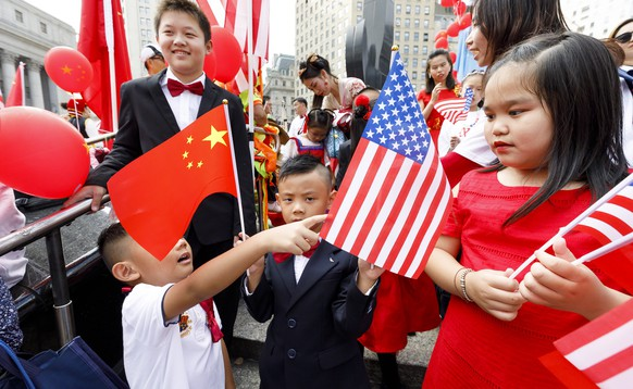epa07886979 Children hold Chinese and US flags during a celebration held by the area?s Chinese-American community for China's National Day, which commemorates the founding of People's Republic of China in 1949, in New York, New York, USA, 01 October 2019.  EPA/JUSTIN LANE