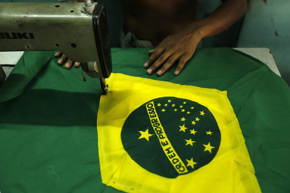 epa04218669 A tailor sews Brazilian national flags to sale to supporters ahead of the FIFA World Cup Football in a shop in Dhaka, Bangladesh, 22 May 2014. Bangladesh has huge supporters of both Brazil and Argentina. The event will kick off in Brazil with the participation of 32 nations on 12 June 2014.  EPA/ABIR ABDULLAH