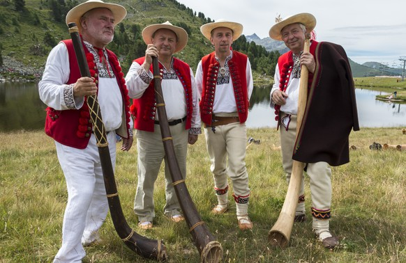 Representants of the Polish group with a pastoral horn pose for the photographer in front of the Lake Tracouet during the 14th international alphorn festival in Nendaz, Valais, Switzerland, Sunday, July 26, 2015. Due to the bicentenary of the host Canton Valais, an exceptional number of 200 alphorn players have been invited for this year's edition of the alphorn festival. (KEYSTONE/Dominic Steinmann)