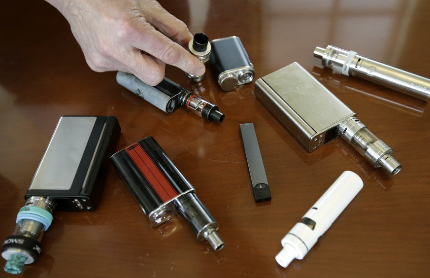 FILE - In this April 10, 2018, file photo, a high school principal displays vaping devices that were confiscated from students in such places as restrooms or hallways at the school in Massachusetts. The U.S. surgeon general says swift action is needed to prevent millions of teenagers and adolescents from becoming hooked on Juul and other high-nicotine electronic cigarettes. Surgeon General Jerome Adams said Tuesday, Dec. 18, that parents, teachers and physicians must take aggressive steps to address an epidemic of underage vaping. (AP Photo/Steven Senne, File)