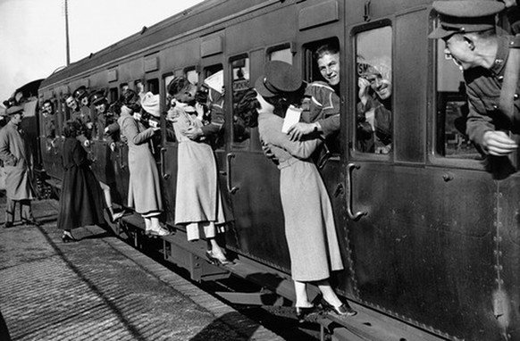 Leaning out of train windows at Feltham Station, soldiers departing for Egypt kiss their wives and girlfriends goodbye. September 1935.
