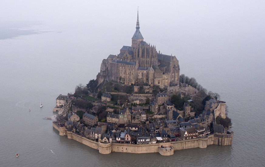 FILE - In this March 21, 2015 file photo, a high tide submerges a narrow causeway leading to the Mont Saint-Michel, on France's northern coast. Authorities are evacuating tourists and others from the Mont-Saint-Michel abbey and monument in western France on Sunday April 22, 2018, after a visitor apparently threatened to attack security services. (AP Photo) FRANCE OUT