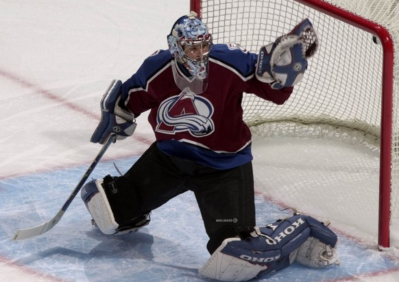 Colorado Avalanche back-up goalie David Aebischer reaches out to stop a shot off the stick of the Vancouver Canucks in the first period in Denver on Thursday, Oct. 25, 2001. Aebischer, who is from Switzerland, was starting his second straight game in the net for the Avalanche since stasrting goalie Patrick Roy is sidelined with a sore hip. (AP Photo/David Zalubowski)